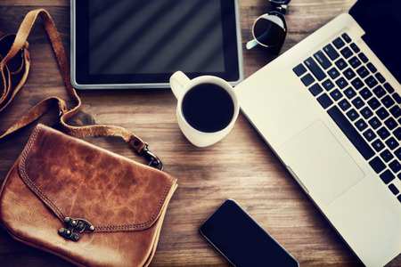 business lifestyle: Working place: laptop, tablet, phone, cup of coffee and stylish bag on the table of a business woman, lifestyle of modern people concept