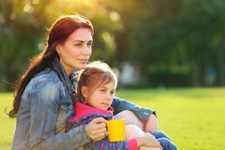 convivencia familiar: Retrato de una madre joven y bella con la pequeña hija linda que se relaja al aire libre, beber té por la mañana, con el tiempo el gasto placer juntos en el campo, la vida familiar feliz