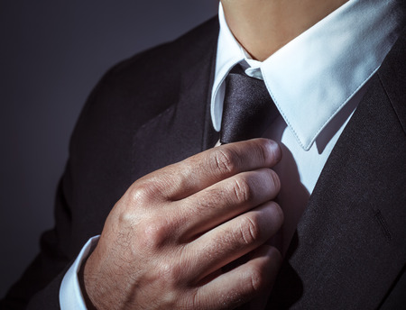 Closeup photo of a man wearing stylish black suit and tie over dark background, body part, mens fashion concept Foto de archivo