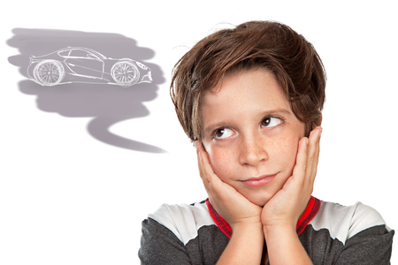 dreaminess: Closeup portrait of a cute teen boy dreaming about a car, thoughtful child isolated on white background, great boyish wish