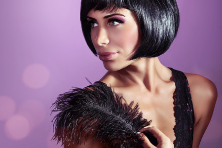young womens: Portrait of an attractive stylish model posing with black feather over purple background, stylish bob haircut and colorful makeup, retro fashion look Stock Photo
