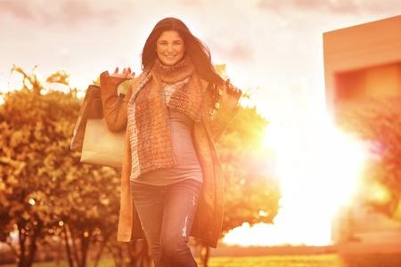 mujeres felices: Alegre mujer embarazada con bolsas de la compra en el jardín en día de sol brillante, la venta estación del otoño, haciendo la compra para un bebé, período de embarazo feliz