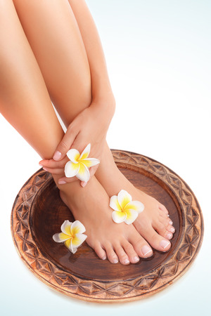 Women's health: Beautiful womens legs and frangipani flowers over white blue background, beauty treatment, perfect skin waxing, pedicure in spa salon