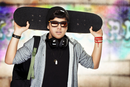 boy skater: Stylish teen boy with skateboard, urban graffiti wall background, active handsome guy listening music, modern life of young people