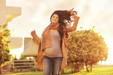 buyer: Pregnant woman after shopping, happy expectant girl with paper bags going home, mild sunset light, enjoying great autumn sale