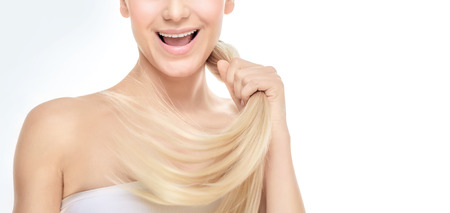 Face part of a happy blond girl with healthy shiny glossy hair over white grey background, photo with copy space, healthy hair concept