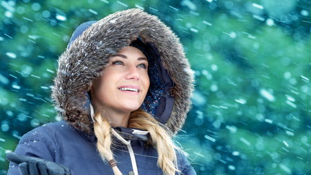 fur hood: Portrait of a nice woman in winter park enjoying falling snow, wearing warm coat with fur hood, happy wintertime holidays