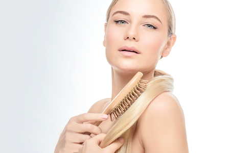 Portrait of a gorgeous woman over clear background combing her blond hair with wooden hairbrush, fashion model wearing natural makeup Stock Photo