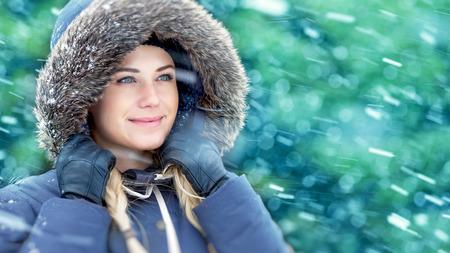 fur hood: Closeup portrait of a beautiful woman enjoying winter, wearing warm coat with fur hood in snowy weather outdoors, wintertime holidays Stock Photo