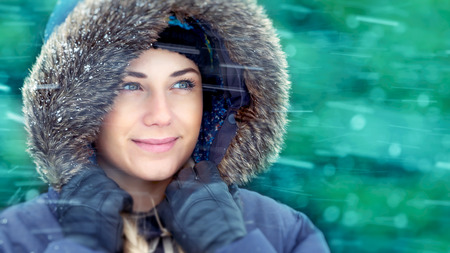 Closeup portrait of a beautiful woman enjoying snow, wearing warm coat with fur hood in snowy weather outdoors, winter holidays