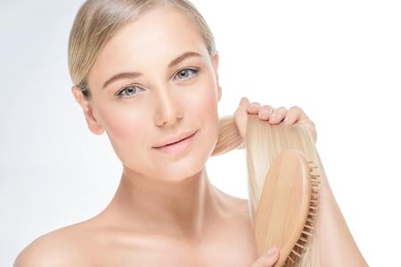 Portret van een zachte blonde vrouw haar haren kammen die op grijze witte achtergrond, behandeling in de spa salon, gezond haar en huid Stockfoto