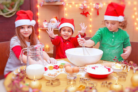 Happy children making Christmas cookies at home, cute little kids wearing red Santa Claus hats, preparing festive sweets, traditional celebration of winter holidays