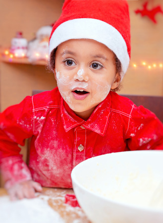 Portrait of a cute little boy soiled in flour, wearing red Santa hat making Christmas cookies at home, happy festive time, preparation for winter holidays