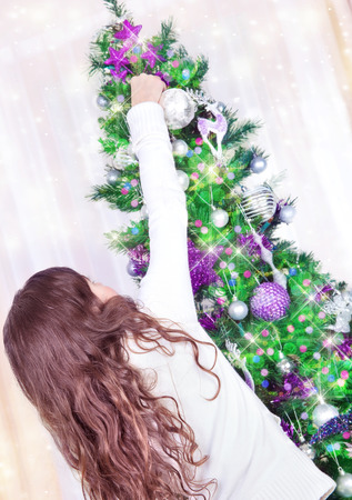 Teen girl decorating Christmas tree at home, festive party in Xmas eve, winter holidays, happy childhood photo