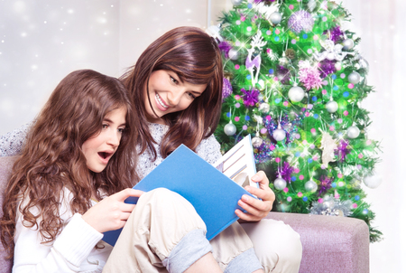 Happy family near Christmas tree, mother and daughter reading book on Christmas eve at home, enjoying interesting exciting fairy tale photo