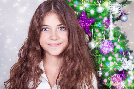 Portrait of a cute teen girl near beautiful decorated Christmas tree at home, festive party in Xmas eve, happy winter holidays photo