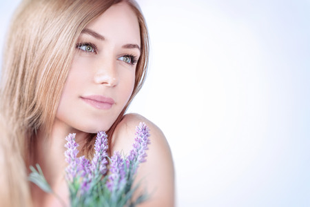 Belle femme au spa, closeup portrait d'une belle jeune fille blonde en appréciant l'arôme d'une fleur de lavande sur fond clair, en utilisant des produits cosmétiques naturels, mode de vie sain