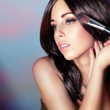 Closeup portrait of a beautiful woman with shiny glossy hair doing makeup over colorful background, applying brush for powder, perfect fashion look photo