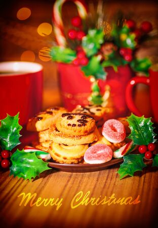 chocolate treats: Merry Christmas greeting card, beautiful cozy festive sweets still life, tasty homemade cookies with two cups of hot chocolate on the wooden table, delicious treats for Santa  Stock Photo