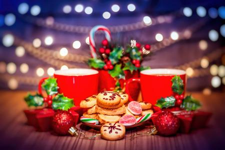santa cena: galletas de Navidad, café caliente y sabrosa casa pan de jengibre decorado con la baya santa y festivo juguetes sobre la mesa, sobre el fondo de la pared hermosa decoradas con brillante guirnalda
