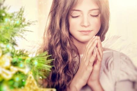Primer retrato de una hermosa chica tranquila con los ojos cerrados rezando cerca del árbol de navidad, ángel joven gentil que deseen la paz y la armonía para todo el mundo, día de fiesta religioso feliz