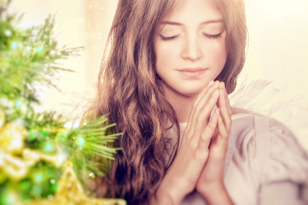 Closeup portrait of a beautiful calm girl with closed eyes praying near Christmas tree, gentle young angel wishing peace and harmony for everyone, happy religious holiday Archivio Fotografico