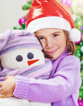 Closeup portrait of a cute little baby girl wearing red Santa hat near festive decorated Christmas tree, with love hugging her soft snowman toy, enjoying Xmas present, happy winter holidays Stock Photo