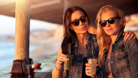 Portrait of a two beautiful girls spending leisure time in the outdoor cafe with drinks, models wearing stylish sunglasses, enjoying bright sunny day Imagens