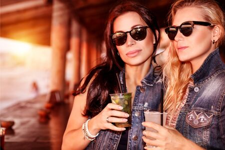 night out: Two gorgeous women with refreshing drinks having fun in the beach cafe, wearing stylish sunglasses and enjoying beautiful sunset, best friends with pleasure spending time together Stock Photo