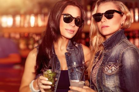 mujeres fashion: Dos mujeres hermosas con bebidas refrescantes que se divierten en el bar al aire libre, con gafas de sol con estilo y disfrutando de hermosa puesta de sol, mirada de la manera de dos mejores amigos Foto de archivo