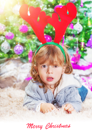 christmastime: Little boy lying down near Christmas tree at home, little Santa helper, reindeer Rudolf head accessory, Christmastime photo with text space, best wishes on winter holidays Stock Photo