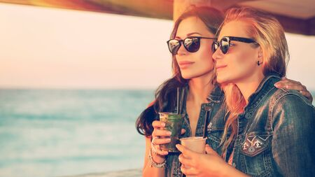 young womens: Portrait of a two beautiful girls spending leisure time in the outdoor cafe, drinking tasty cocktails and enjoying beautiful sea view in bright sunny day