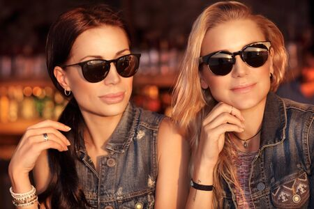 Portrait of a two gorgeous woman outdoors at night, beautiful friends going out, wearing stylish jeans jackets and sunglasses over glowing city lights background Stock Photo