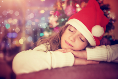 Portrait of a beautiful teen girl wearing red Santa hat sleeping near Christmas tree in anticipation of a gifts and Santa Claus, Xmas eve, happy winter holidays photo
