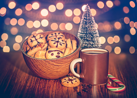 sweet treats: Christmas cookies with coffee cup on the wooden table and Christmas decoration over bokeh background, beautiful festive still life, sweet treats for Santa Claus