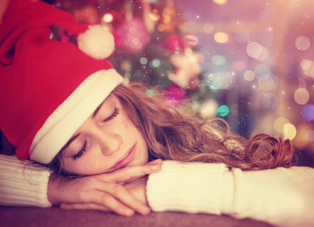 Closeup portrait of a nice girl waiting for a Christmas gifts, tired child wearing red Santa hat sleeping in the decorated room at home, winter holidays concept photo