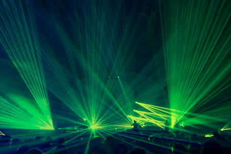 People on the party enjoying concert, dancing in the night club, celebrating new year eve,bright green laser light background