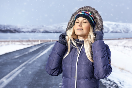 closed eye: Portrait of a beautiful smiling girl with closed eyes enjoying winter travel on the cold snowy day, happy woman traveler, Iceland