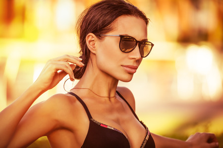 Portrait of a beautiful woman on the beach, attractive model wearing stylish sunglasses, fashion look for summer vacation on the beach