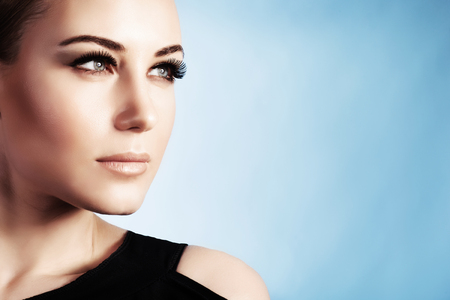 Nahaufnahme Porträt einer schönen Frau isoliert auf blauem Hintergrund, wunderschöne Mädchen mit perfekten Make-up, gut aussehende Modell