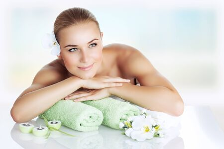 sitting pretty: Portrait of a nice woman at spa, beautiful girl lying down on a massage table and enjoying health and beauty procedure, relaxation and pleasure concept