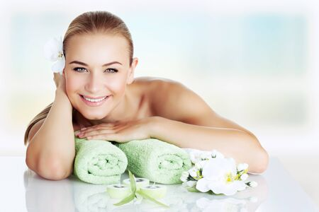 young womens: Portrait of a beautiful smiling woman lying down on massage table, happy and healthy vacation in the wellness hotel, enjoying pleasant procedure at spa salon Stock Photo
