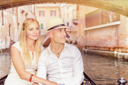 Portrait of a nice couple sitting in the gondola and enjoying wonderful trip along canal on narrow Venice street, romantic travel to Italy, Europe photo
