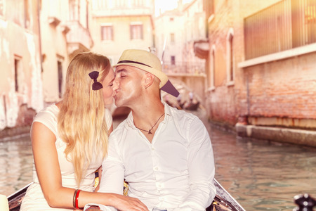 Gentle couple in love, newlywed traveling and kissing in gondola on the water in Venice, romantic relationship, enjoying honeymoon in Italy, Europe photo
