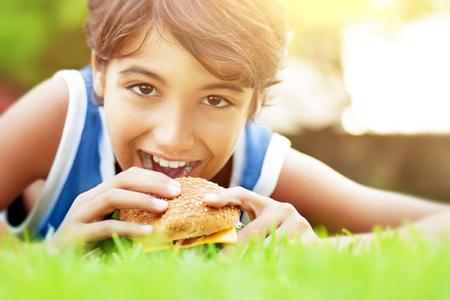 niños desayunando: Retrato del primer de un muchacho lindo adolescente feliz acostado en la hierba verde y comer deliciosa hamburguesa, disfrutando sabroso almuerzo al aire libre, el tiempo feliz en el campamento de verano Foto de archivo