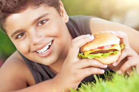 niños desayunando: Primer retrato de un niño feliz linda adolescente acostado en la hierba verde y comer deliciosa hamburguesa, disfrutar de un almuerzo sabroso en día soleado, el tiempo feliz en el campamento de verano