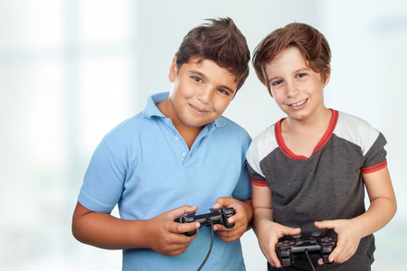 Portrait of a two cute happy boys playing video games at home, best friends enjoying competition on playstation, with pleasure having fun together