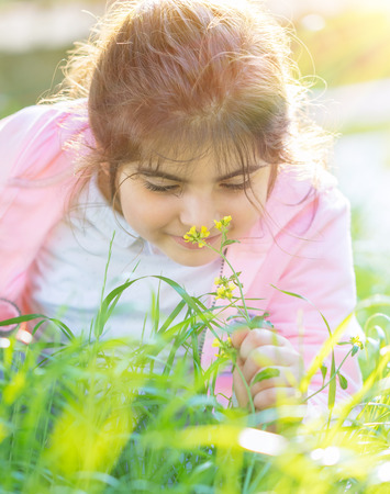 Portrait of a little girl enjoying flower aroma, having fun on fresh green grass field in spring sunny day, cute child with pleasure spending time outdoors Imagens