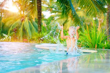 Happy boy having fun in swimming pool, joyful kid splashing water from the pool, spending summer holidays on the luxury beach resort
