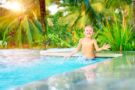 Cute happy little boy playing in the pool in nice sunny day, splashing water in the swimming pool, having fun on the beach resort, spending summer holidays with pleasure photo